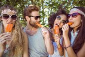 stock photo of lolli  - Hipster friends enjoying ice lollies on a summers day - JPG