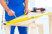 foto of workbench  - Midsection of carpenter working at workbench in bright office - JPG