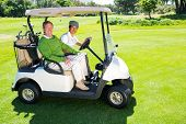 picture of buggy  - Golfing friends driving in their golf buggy smiling at camera at the golf course - JPG