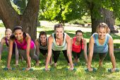 stock photo of work boots  - Fitness group planking in park on a sunny day - JPG