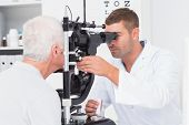 stock photo of slit  - Male optometrist examining senior mans eyes through slit lamp in clinic - JPG