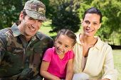 picture of reunited  - Handsome soldier reunited with family on a sunny day - JPG