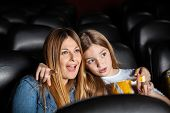 image of watching movie  - Cute girl showing something to shocked mother while watching movie in cinema theater - JPG