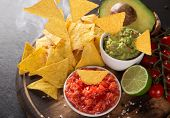 stock photo of nachos  - Guacamole with nachos in freeze motion - JPG
