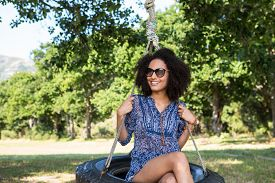 stock photo of tire swing  - Pretty young woman in tire swing on a summers day - JPG