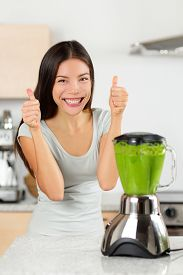 picture of blender  - Vegetable smoothie woman happy thumbs up blending green smoothies with blender home in kitchen - JPG