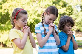 image of prayer  - Children saying their prayers in park on a sunny day - JPG
