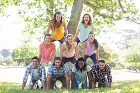 picture of human pyramid  - Happy friends in the park making human pyramid on a sunny day - JPG