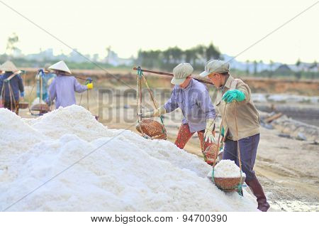 Ninh Hoa, Vietnam - March 2, 2012: Vietnamese Women Are Burdening Hard To Collect Salt From The Extr