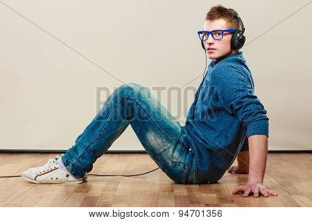 Young Man With Headphones Sitting On Floor
