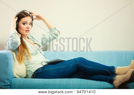 Woman With Tablet Headphones Sitting On Couch