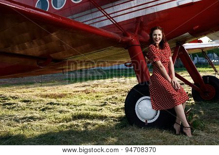 pin-up female sitting on plane wheel in dress