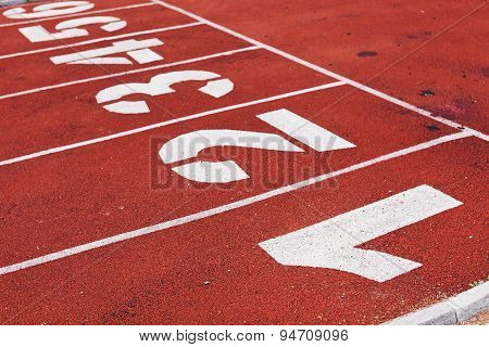 Red running path with white lines numbers in perspective
