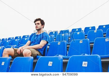 Attractive male model in blue shirt relaxing sitting on blue chairs on stadium