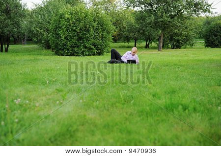 Businessman With Laptop Lying On Green Grass