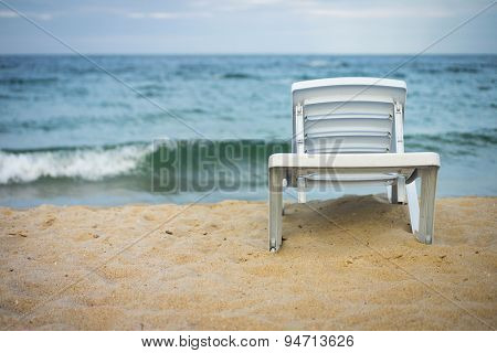 Plastic White Lounge Chair On Empty Beach
