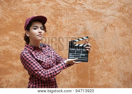 Young Woman With Movie Clapper Behind Orange Wall
