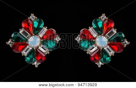 earring with colorful red and green gems on black background