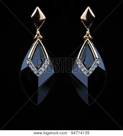 earring with colorful black gems on black background