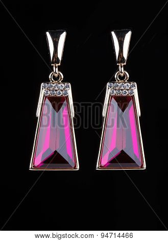 earring with colorful pink gems on black background