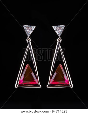 earring with colorful red gems on black background