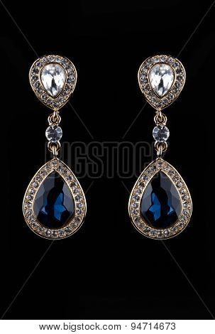 earring with colorful blue gems on black background
