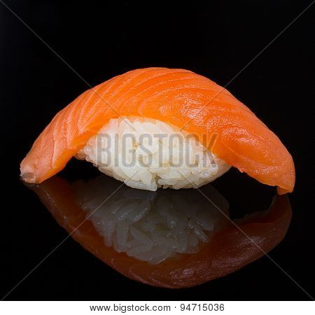Salmon sushi nigiri clodeup over black background with reflection