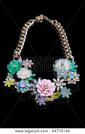luxury necklace of plastic flowers on black stand
