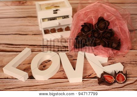 Mini Chocolate Sweets And Love Letters On A Wooden Table