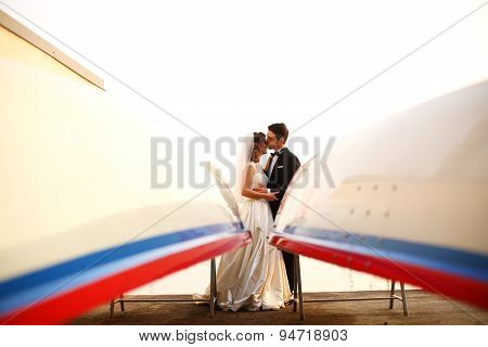 Bride And Groom Embracing Near Big Boat