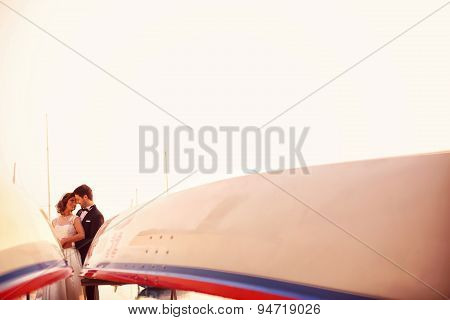 Bride and groom embracing near boats