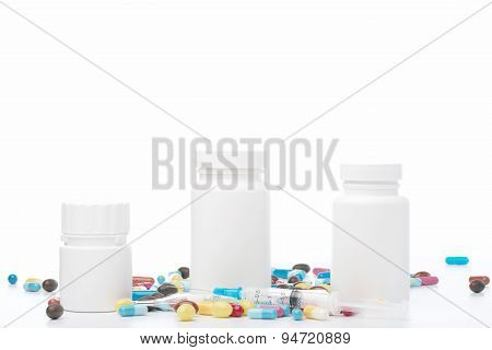 White pill bottle and colorful pills on white background