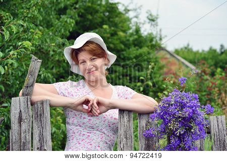 Woman With   Wildflowers Near  Wooden Fence In The Village