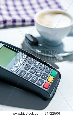 Payment Terminal In The Restaurant. Coffee In The Background