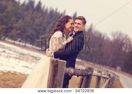 Bride And Groom Embracing Near Forest