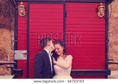 Bride And Groom Against Red  Door