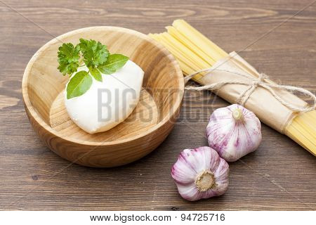 Noodles in paper tied with a rope, a wooden bowl mozzarella, fresh herbs and fresh vegetables