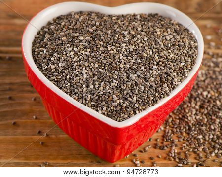 Chia Seeds In  Heart Shaped Bowl On  Wooden Table.
