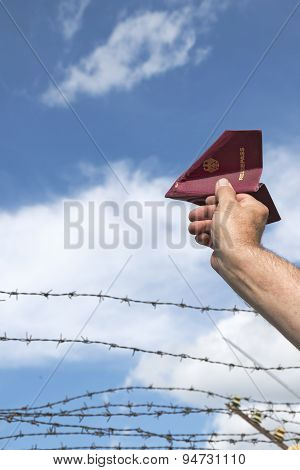 Man's Hand Holding His Passport As A Paper Airplane  Over A Barbed Wire Fence