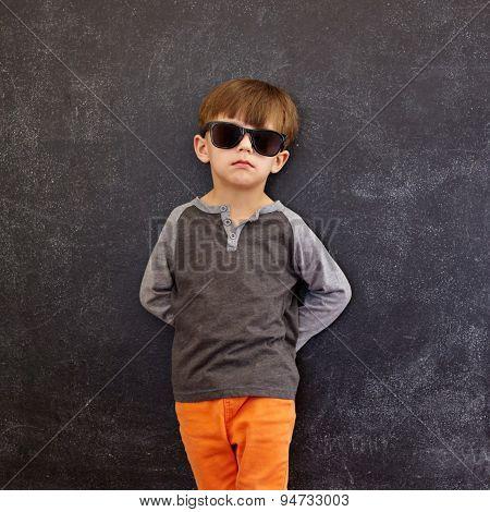 Stylish Little Boy Wearing Sunglasses Leaning On A Blackboard