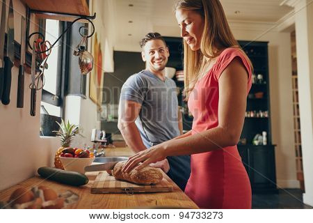 Couple In The Kitchen With Woman Cutting Bread