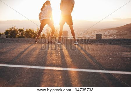 Couple Of Joggers Standing On Hillside In Morning