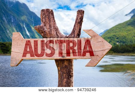 Austria wooden sign with countryside background