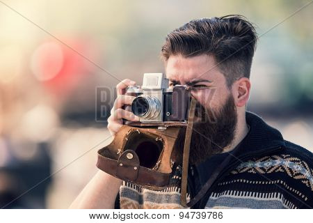 Trendy hipster young man holding vintage camera