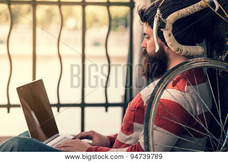 Trendy hipster young man with modern laptop. sitting in front of bike