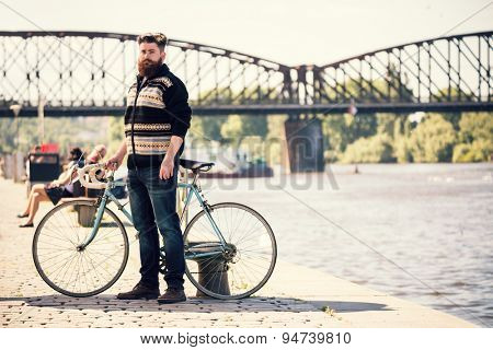 Trendy hipster young man with bicycle, Posing next to river