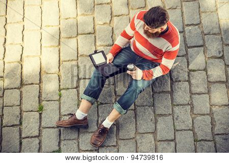 Trendy hipster young man with digital book and smart phone. Shot from aerial view