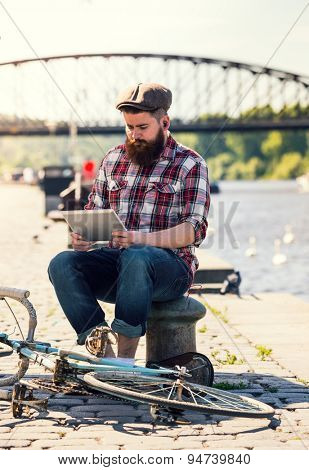 Trendy hipster young man using tablet. Sitting on sidewalk