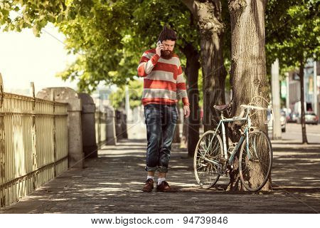 Trendy hipster young man with bicycle and using smart phone
