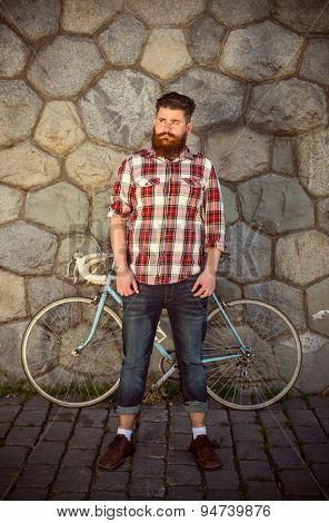 Trendy hipster young man with bicycle, Posing in front of stone wall